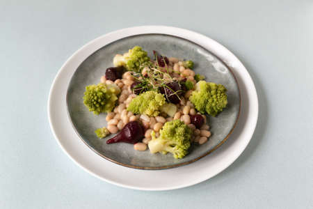 Natural salad of mini beets, romanesco cabbage, white beans and sprouted onion seeds on a gray plate. Healthy nutrition concept. Selective focus. Copy space.