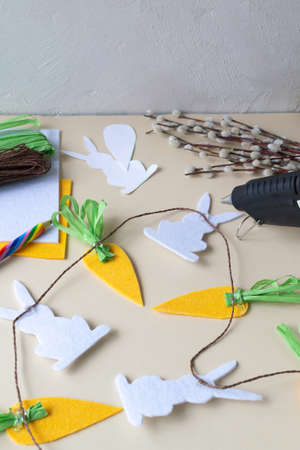 How to make an Easter garland of rabbits and carrots with your own hands from felt. Step by step instruction. Step 10. We put all the elements on a brown paper cord. Imagens