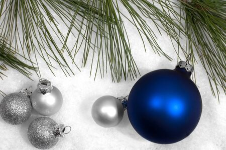 Silver and blue Christmas ornament display with pine branch Stock Photo