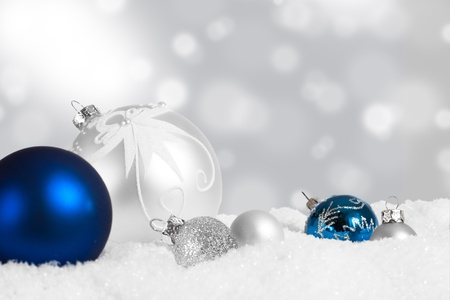 Silver and blue Christmas ornament display in snow photo