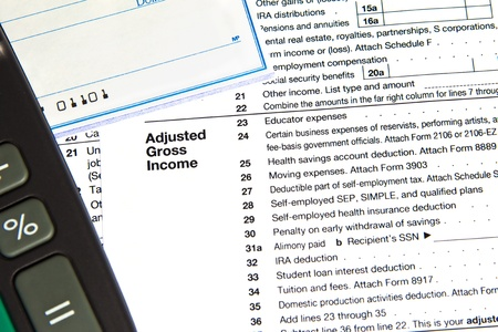 adjusted: Tax document showing adjusted gross income with checkbook and calculator Stock Photo
