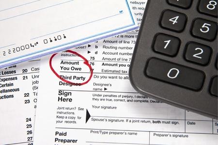 chequera: Documento fiscal - Importe que debe en la declaración de impuestos con el talonario de cheques y la calculadora Foto de archivo