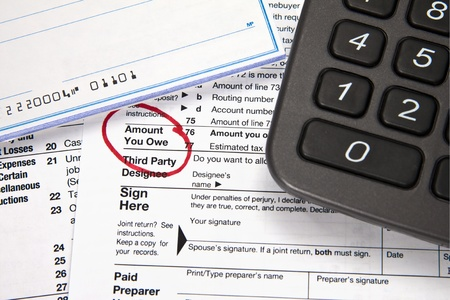 adjusted: Tax document - Amount you owe on tax return with checkbook and calculator