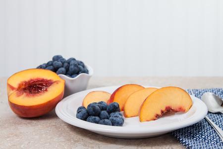 白い皿にスライスした桃とブルーベリーを提供しています 写真素材