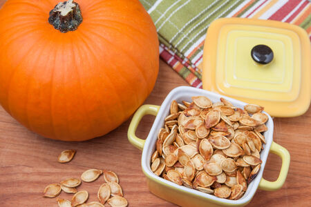 pumpkin seeds: Toasted pumpkin seeds with a fresh pumpkin on a wooden cutting board