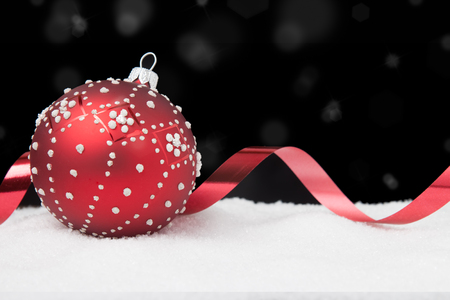 Red and white Christmas ball and ribbon on a black background
