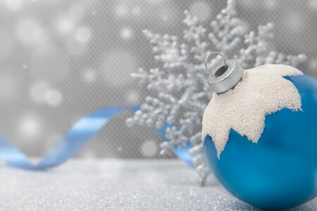 A single blue Christmas snow-capped ornament sits with a snowflake and ribbon on a glittery surface