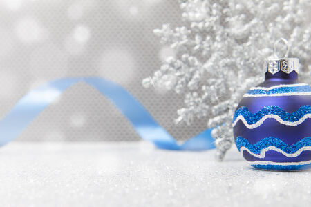 A single blue Christmas ornament sits with a snowflake and ribbon on a glittery surface