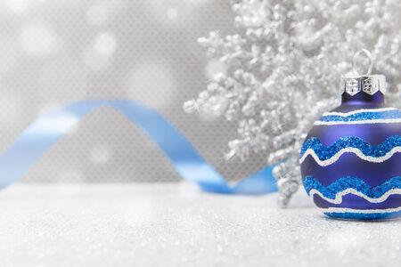 Un seul ornement de Noël bleue est assis avec un flocon de neige et le ruban sur une surface pailleté Banque d'images - 33945271