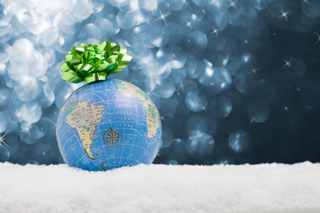 World globe rests in the snow with a bow and starry night background Stockfoto