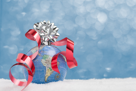 World globe sits in snow on blue twinkle background with ribbon and bow