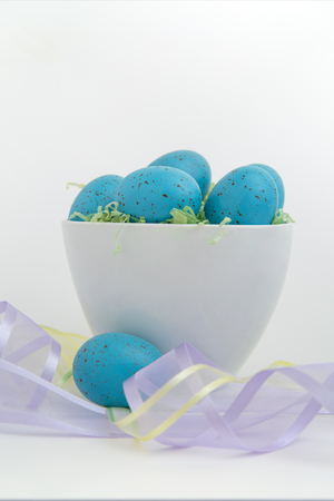 Brightly colored blue eggs in a white bowl with sheer pastel ribbons photo