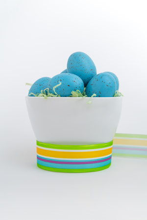 Brightly colored blue eggs in a white bowl encircled by vibrant ribbon on a white background photo