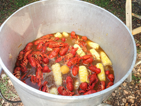 A boiling pot of crawfish, corn, potatoes and seasoning being cooked outdoors in a large kettle Archivio Fotografico