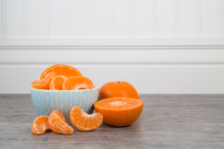 Mandarin orange slices in a blue bowl on a wooden table with unsliced orange nearby