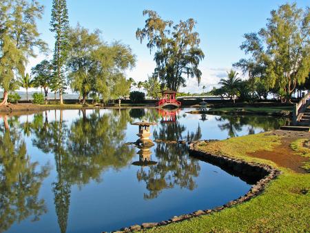ponte giapponese: Un ponte giapponese rosso si riflette nelle acque calme del lago a Hilo Hawaii Archivio Fotografico