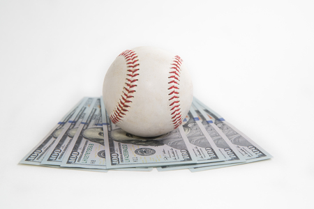Baseball sits atop hundred dollar bills to represent the cost of sports