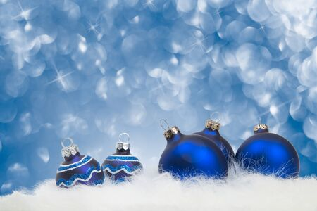 Arrangement of blue Christmas ornaments on white fur with blue twinkling background
