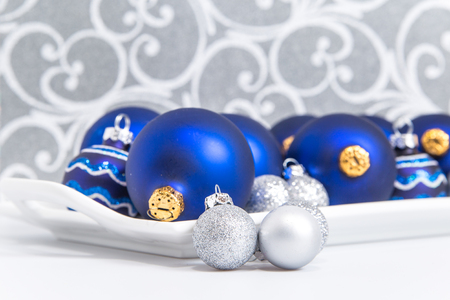 blue and silver christmas ornaments on a tray with silver swirls in background stock photo - Blue And Silver Christmas Ornaments