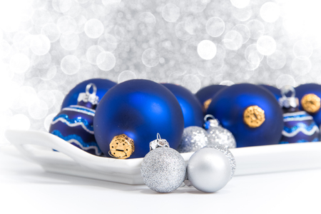 Blue and silver Christmas ornaments on a tray with sparkling lights in background