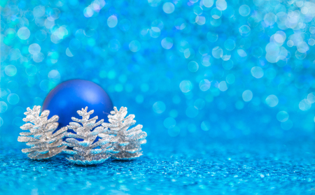 Blue christmast ornament and silver pinecones on sparkling blue backcground Stock Photo