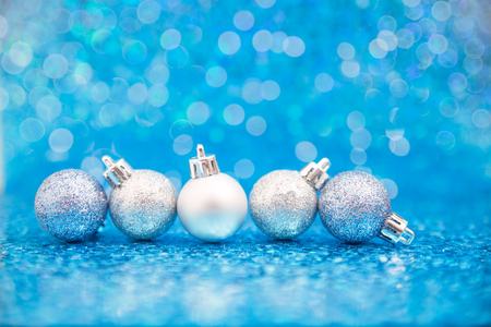 Line of silver blue glittering ornaments on sparkling blue background