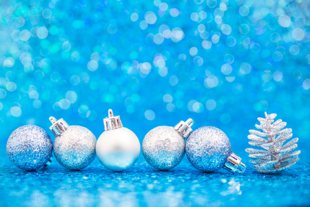 Line of silver blue glittering ornaments and a pinecone on sparkling blue background