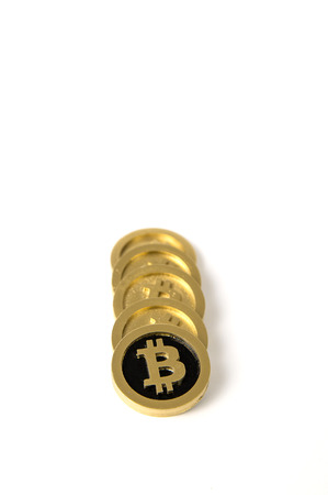 Stack of golden coins with the bitcoin symbol on  white background