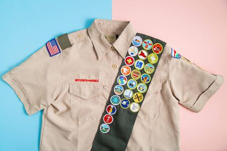 SAINT LOUIS, UNITED STATES - MAY 3, 2018:  Boy Scouts of America (BSA) uniform shirt and merit badge sash on pink and blue background as BSA welcomes girls to join scouting Banque d'images - 140057101