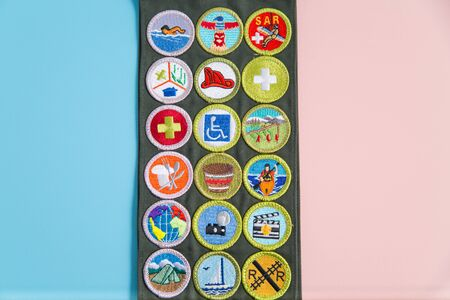 SAINT LOUIS, UNITED STATES - MAY 3, 2018:  Boy Scouts of America (BSA) merit badge sash on pink and blue background as BSA welcomes girls to join scouting