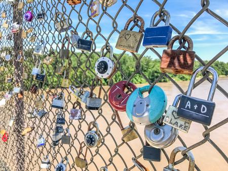 Padlocks line a chainlink fence along a Missouri riverfront bike trail Stock Photo