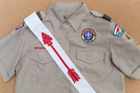 SAINT LOUIS, UNITED STATES - AUG 21, 2018:  Boy Scouts of America (BSA) uniform shirt and Order of the Arrow sash on a cork brown  background Éditoriale