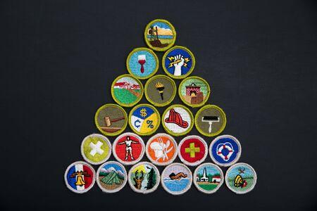 SAINT LOUIS, UNITED STATES - AUG 22, 2018:  A pyramidal arrangement of Boy Scouts of America (BSA) merit badges on black background