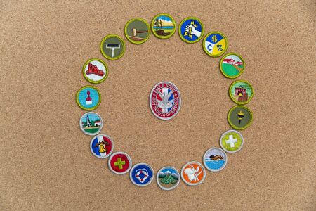 SAINT LOUIS, UNITED STATES - AUG 22, 2018:  A circular arrangement of Boy Scouts of America (BSA) merit badges with Eagle badge on cork background