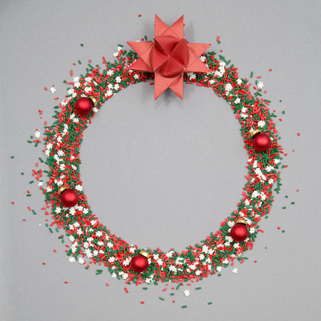 Christmas wreath made of red and green sprinkles with christmas ornaments on a grey background Stock Photo