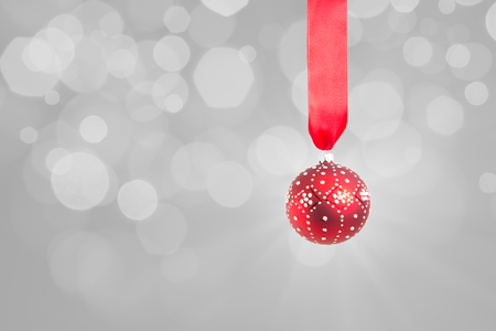 A red ornament suspended on a red ribbon on a grey background with out of focus lights in background