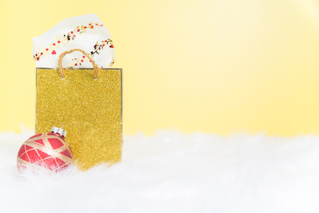 A stuffed gold sparkly  gift bag on white fur with a yellow background