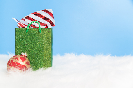A stuffed green sparkly  gift bag on white fur with a blue background Stock Photo