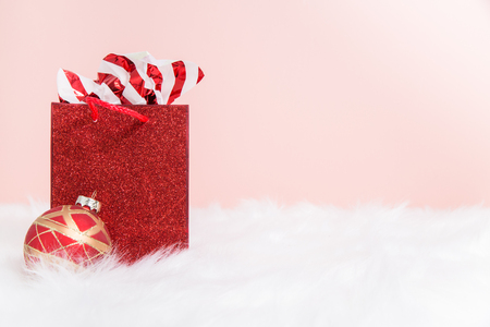 A stuffed red sparkly  gift bag on white fur with a pink background