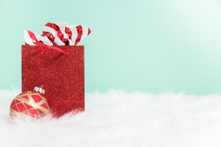 A stuffed red sparkly  gift bag on white fur with a green background