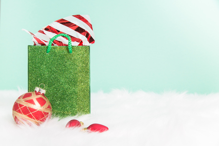 A stuffed green sparkly  gift bag on white fur with a green background Stock Photo