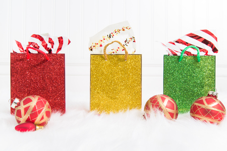 Three glittery gift bags in a row on a white background and fur with red and gold Christmas ornaments