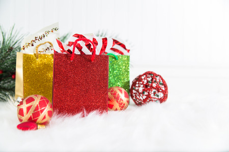 A trio of glittery gift bags on white background and fur with red and gold Christmas ornaments