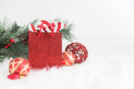 A red glittery gift bag on white background and fur with red and gold Christmas ornaments
