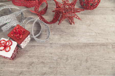 Red and white Christmas packages with glittery ribbon and decorations on grey rustic wood table