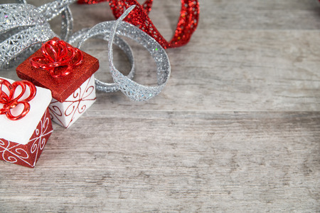 Red and white Christmas packages with glittery ribbon on grey rustic wood table Stock Photo