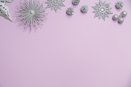 Flat lay of silver glitter snowflakes, stars, ornaments and pinecones arranged in a border on a pale purple pink background