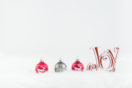 Christmas ornaments in red and grey with word sign joy on fur rug with white background