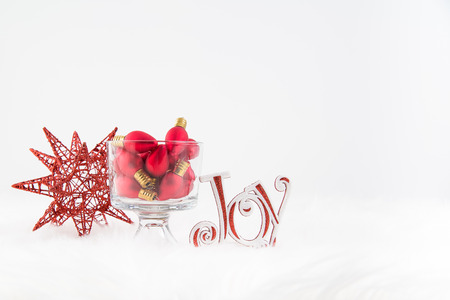 Christmas ornaments in red on fur rug with white background Stock Photo