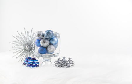Christmas ornaments in silver and blue on fur rug with white background Stock Photo